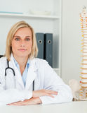 Serious doctor with model spine next to her looks Royalty Free Stock Image