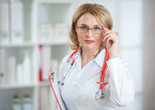 Serious doctor or pharmaceutist woman in glasses Stock Images