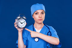 Serious doctor pointing at alarm clock Royalty Free Stock Image