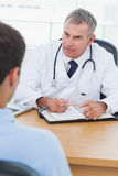 Serious doctor prescribing drug to his patient Stock Images