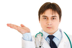 Serious doctor presenting something on empty hand Stock Photography