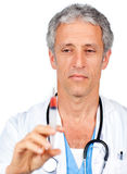 Serious doctor presenting a syringe Royalty Free Stock Photos