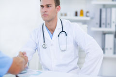 Serious doctor shaking hands Stock Images