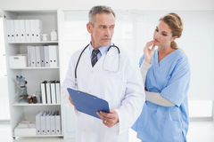Serious doctor showing nurse a chart Royalty Free Stock Images