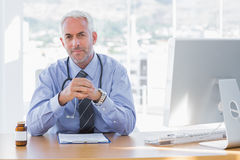 Serious doctor sitting at his desk Stock Photo