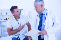Serious doctor speaking with his patient Stock Photos