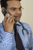 Serious doctor speaking on mobile phone. With worried look Stock Photography
