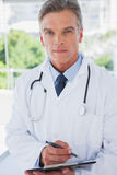 Serious doctor standing with a clipboard royalty free stock photography