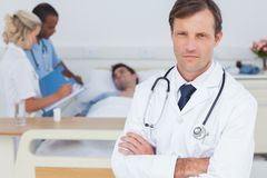 Serious doctor standing and looking at the camera Stock Photos