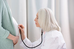 Serious doctor with stethoscope listening belly of pregnant woman. Side view of serious doctor with stethoscope listening belly of pregnant woman Stock Photos