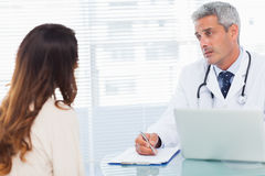 Serious doctor talking with his patient and writing on a notebook stock photography