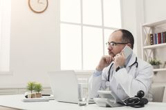 Serious doctor talking on phone with his patient stock images