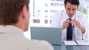 Serious doctor talking to his patient while sitting