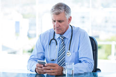 Serious doctor texting with his mobile phone Royalty Free Stock Photography
