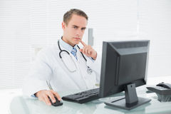 Serious doctor using computer at medical office Royalty Free Stock Images