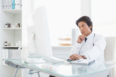 Serious doctor using the computer Royalty Free Stock Photography