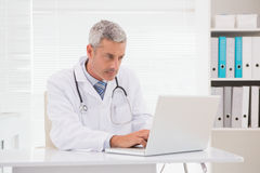 Serious doctor using laptop Stock Photo