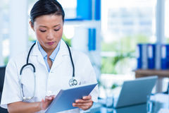 Serious doctor using tablet Royalty Free Stock Photo