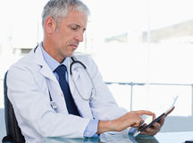 Serious doctor working with a tablet computer Stock Photo