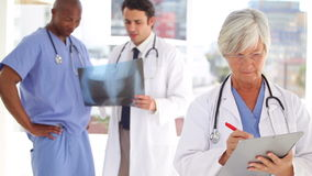 Serious doctor writing on a clipboard in front of her team Royalty Free Stock Image