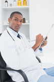 Serious doctor writing a prescription in medical office Stock Photos