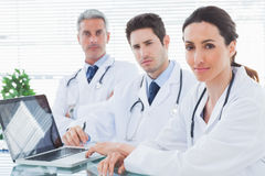 Serious doctors with laptop looking at camera Stock Images