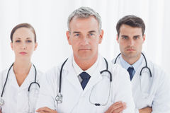 Serious doctors posing together crossing arms Stock Photos