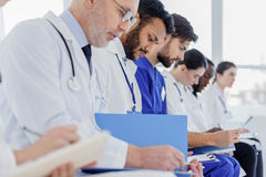 Serious doctors reading documents together. Pensive medical team is analyzing hospital chart with concentration. They are sitting in a row Stock Photography