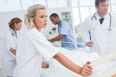 Serious doctors about to walk with patient bed Royalty Free Stock Image