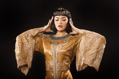 Serious Egyptian woman like Cleopatra with headache, on black background Royalty Free Stock Images