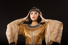 Serious Egyptian woman like Cleopatra with headache, on black background Stock Photo