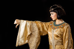 Serious Egyptian woman like Cleopatra with thumbs down gesture, on black background. Thumbs down dislike gesture. Glamorous closeup portrait of beautiful stylish royalty free stock photo