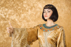 Serious Egyptian woman like Cleopatra with thumbs up gesture, on golden background. Thumbs up. Glamorous closeup portrait of beautiful stylish brunette young stock photo