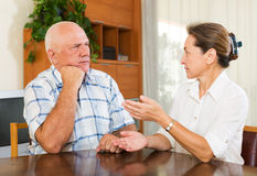 Serious elderly couple talking in home Stock Photography