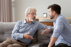 Free Serious Elderly Father And Grownup Son Sitting On Couch Talking Royalty Free Stock Photo - 165812325