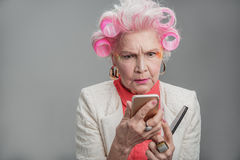 Serious elderly lady holding cellphone and comb Royalty Free Stock Photo