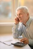 Serious elderly man with calculator Royalty Free Stock Photos