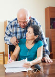 Serious elderly man with wife reading  documents Royalty Free Stock Photography