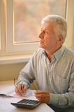 Serious Elderly Man With Calculator Royalty Free Stock Images