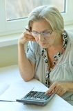 Serious elderly woman with calculator Stock Images