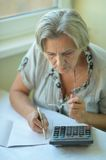 Serious elderly woman with calculator Royalty Free Stock Photography