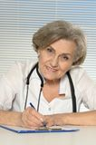 Serious elderly woman doctor. Sitting at table stock images