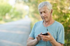 Serious elderly wrinkled male uses smart phone and earphones for listening music, focused into screen, has stroll in countryside, Stock Photos