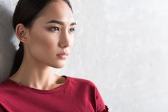 Serious elegant asian girl woman is expressing hopeless. Feeling lonely. Close-up of face of young thoughtful woman is leaning on gray wall and looking aside Royalty Free Stock Images