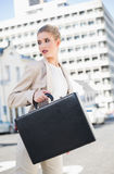 Serious elegant businesswoman holding briefcase Stock Photo