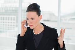 Serious elegant businesswoman using cellphone Stock Images