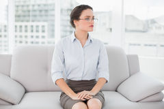Serious elegant woman looking away while sitting on sofa Stock Images