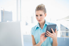 Serious elegant woman using calculator looking at laptop Stock Photography