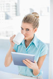 Serious elegant woman using tablet while drinking coffee Stock Images