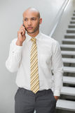 Serious elegant young businessman using cellphone Royalty Free Stock Photo